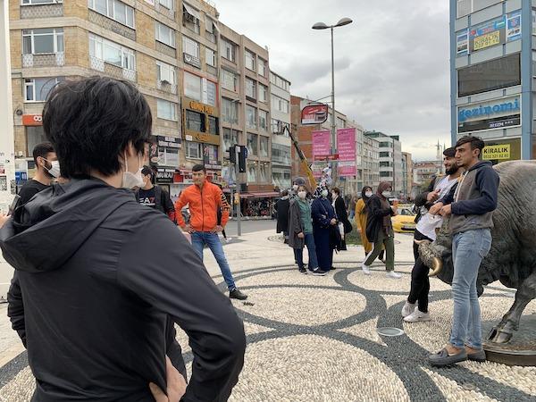カドキョイ広場で写真を撮る若者を見守るにしけい
