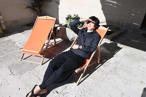 ホテルの部屋前にあるベンチでくつろぐにしけい