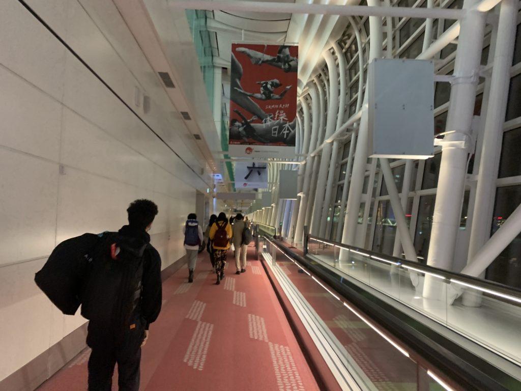 静かな空港内を歩く帰国者たち