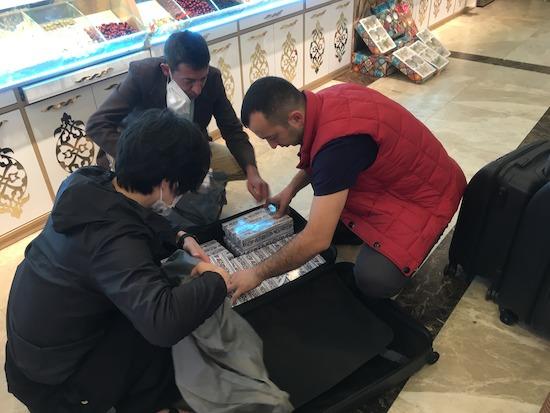 仕入れた商品をスーツケースに詰め込むおじさん3人